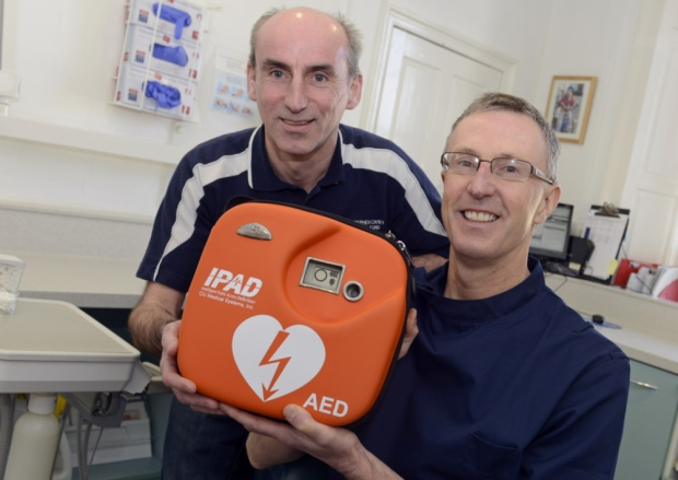 Bryan Shendon hands over a defibrillator to Scott Williamson